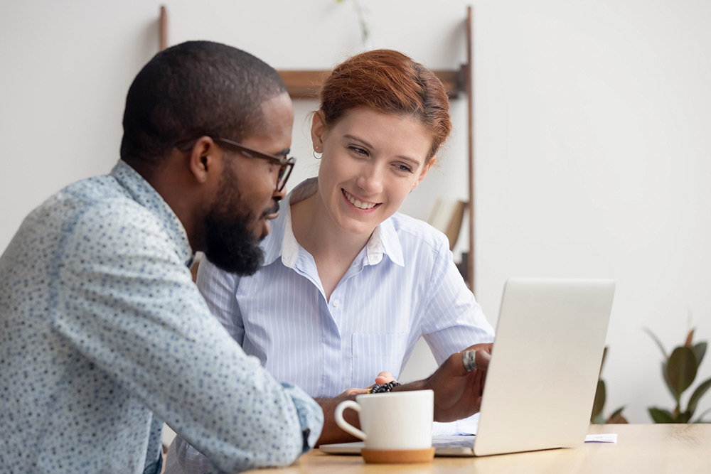 African American man and caucasian woman discuss work in front of a computer